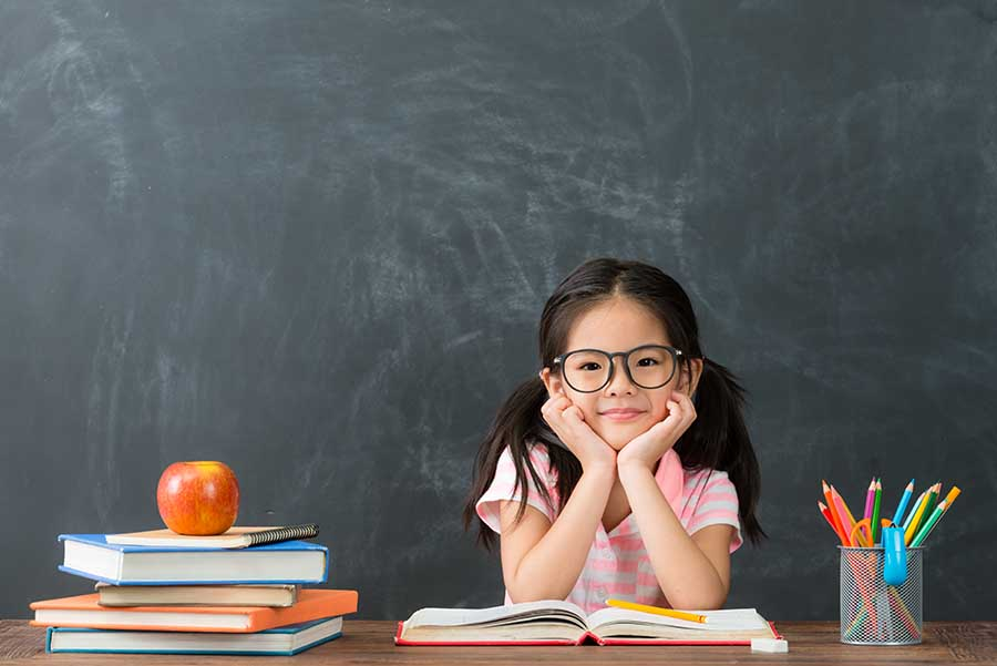 cheerful girl seating at class table with book open