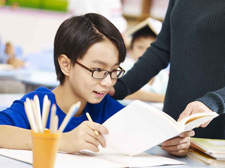 enthusiastic student reading book in tuition class